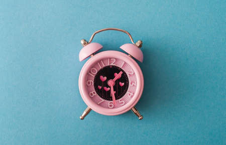 Its time for love management. Pink alarm with heart shape symbols on blue background