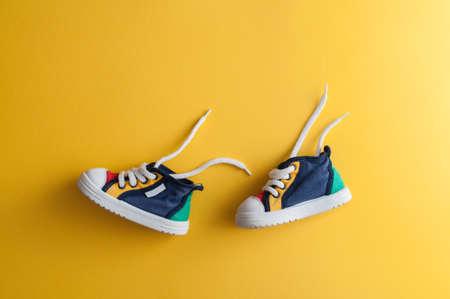 Zapatos de bebé de colores sobre fondo amarillo brillante en la habitación del niño Foto de archivo