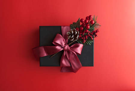 Merry christmas red background with black gift box. Greeting card. Winter holiday. Happy new year. Top view. Flat lay.