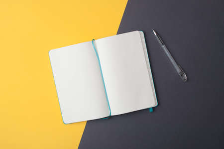 Blank sketchbook and a pen  on yellow gray background flat lay