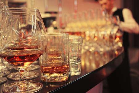 many glasses of alcohol on the bar barman far away