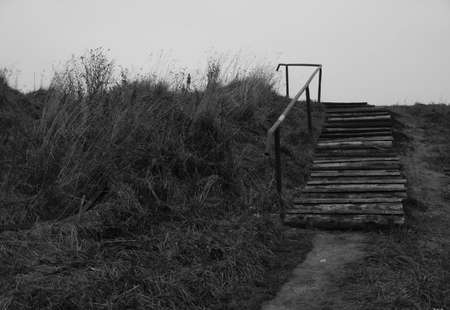 an old wooden stairs leading up to the meadow Stock Photo