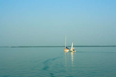 two sailboat with people on board, sunset, lake