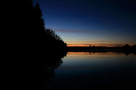 shore of the lake is reflected in the water at night Stock Photo