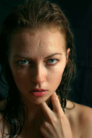 Wet woman portrait with water drops on the face photo