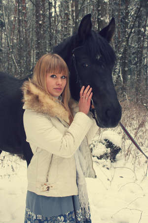 blonde girl with a horse in the winter forest photo