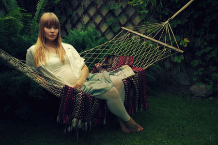 Pregnant woman relaxing in a hammock in the garden Stock Photo