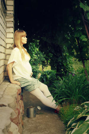 pregnant woman in profile, sitting in the garden