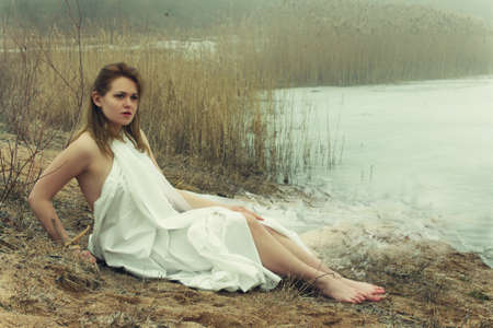 rushy: woman in white dress in the winter on the rushy lake