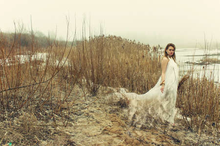 woman in white dress in the winter on the rushy lake photo