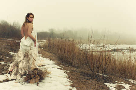 woman in white dress in the winter on the rushy lake