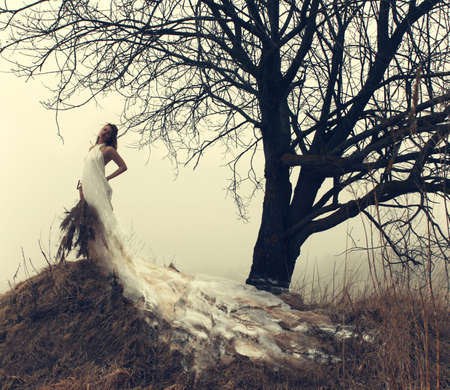 rushy: woman in white dress in the winter on the hill Stock Photo