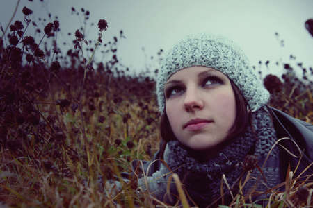 portrait of a girl lying in a meadow autumn in hat and gloves photo