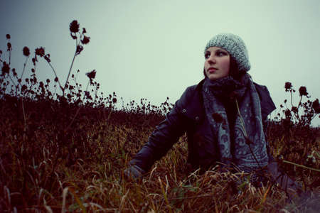 portrait of a girl lying in a meadow autumn in hat and gloves Stock Photo