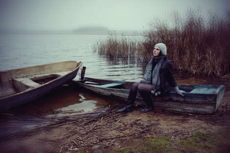 girl sitting on an old boat on the lake shore autumn mist Stock Photo