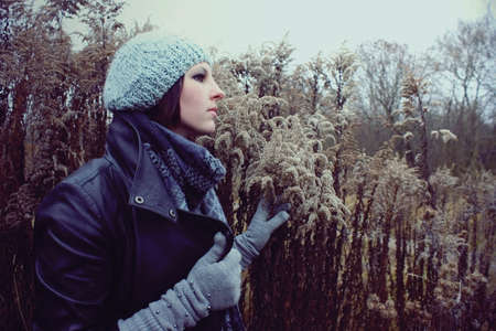portrait of a girl in profile in a meadow autumn in hat and gloves Stock Photo