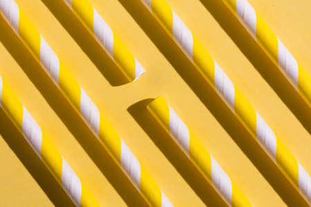 Striped drink straws of yellow colors in row isolated on yellow background. Minimalism concept. Pop art style. Flat lay