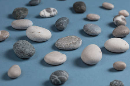 Stones collection. Different kind of pebbles stones with soft shadow on blue background