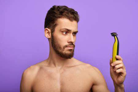se preocupa por la higiene, el hombre está comprobando una nueva afeitadora por la mañana. cerca de la foto