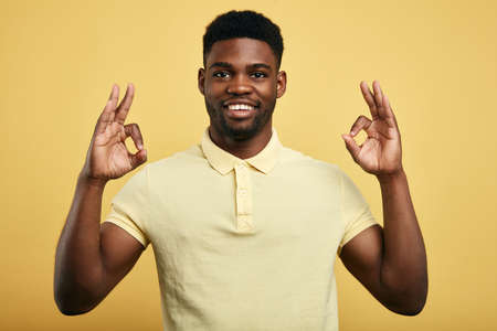 positive guy in stylish T-shirt shows OK gesture with both hands on a yellow background., demonstrating that everything is fine, showing his approval, Body language concept. healthy lifestyle