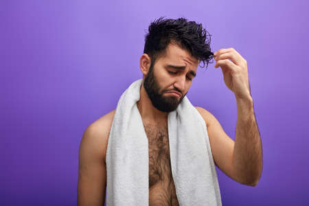 sad emotional man doesnt like his curly hair. close up photo. isolated blue background. Split Ends, Flaky Scalp, Dull Hair
