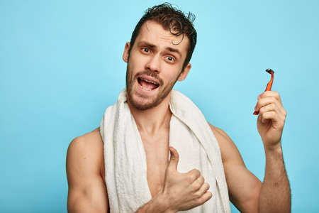 emotional shirtless man going to test anew shaver after bath. close up portrait, isolated blue background