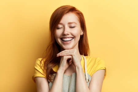 gorgeous ginger girl with closed eyes, joyful and charming smile laughing at somebody, rejoicing at positive news. close up portrait. Stock Photo