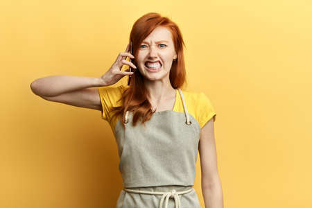 depressed, unhappy, angry, frustrated young woman talking on the phone, isolated over yellow background. Negative human emotions, emotion, problem, feelings. Bad news 写真素材