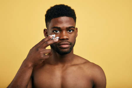 shirtless young brutal african american man applying facial cream on his cheek. close up portrait,mens beauty. skin care Standard-Bild