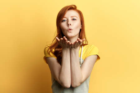 ginger lovely girl in casual outfit sending blowing kiss with lips looking at camera isolated on yellow background.close up portrait. love, flirt concept. feeling, emotion