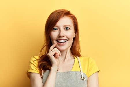 joven atractiva emocionada con un dedo en los labios que componen un gran plan de negocios. Tengo una idea. sueño. Foto de archivo