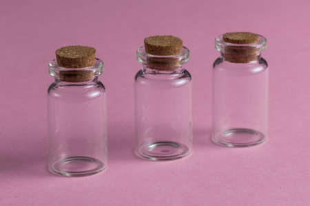 Empty glass medical pharmaceutical sterile bottles for injection on the red background. close up photo
