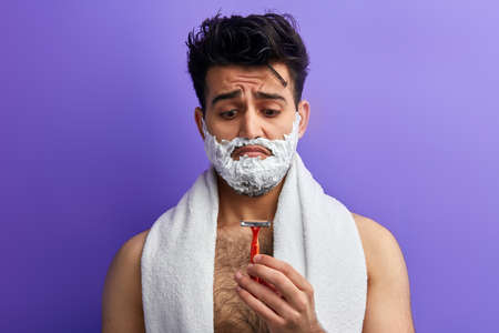 emotional guy isnt satisfied with a razor. close up portrait. sad man has broken the shaver