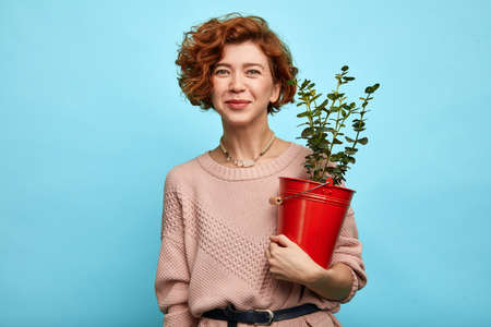 Beautiful cheerful pleasant girl with flower pot isolated on blue background. close up portrait, hobby, lifestyle, pastime