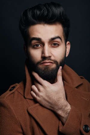 bearded handsome man touching his beard and looking at the camera. stylish macho making decision, planning his day, isolated black background, idea concept Archivio Fotografico