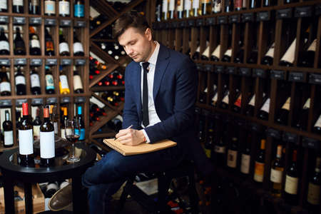 pensive man sommelier with crossed legs writing in notepad somethings at bar. close up side view photo. copy space. job, profession Stock Photo