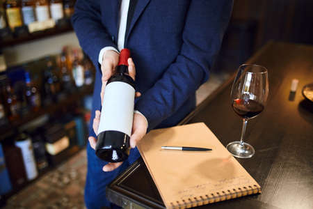 professional talented sommilier choosing bottle of wine. close up cropped photo.would you like a bottle of wine . trade concept