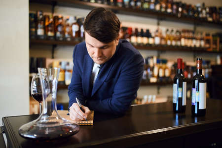 young fashionable man planning the wine menu. close up photo. copy space. the practise of wine tasting 스톡 콘텐츠