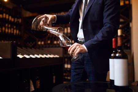 young man mixing wines. creation of unforgettable wine. art concept. close up cropped photo 免版税图像