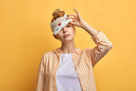 lovely sleepy lady looking through the eyemask . close up portrait. isolated yellow background. sleep loss. lack of sleep