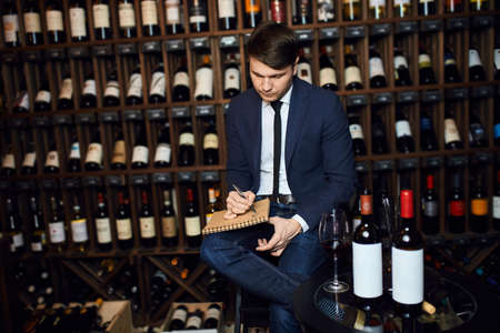 young handsome man managing the inventory of the wine cellar. close up photo Stock fotó