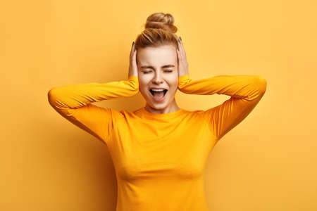 Mujer joven en elegante suéter amarillo gritando de terror con las manos en la cabeza, la boca abierta. concepto de silencio. Deja de hablar. Te odio. emoción y sentimiento Foto de archivo
