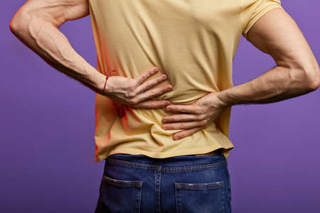 man touching his back, guy has disk peoblems in his back. close up cropped back view photo. isolated blue background