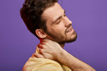 man has cervical rediculopathy. close up cropped photo.whisplash, sudden jolt to the neck . cancer concept. bearded pleasant man massaging his neck.