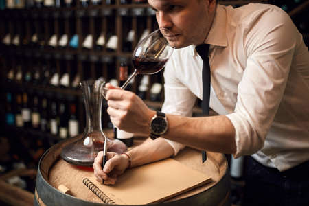 awesome wine steward smelling the wine and writing something on the notebook. close up photo. pleasant unforgettable smell and taste