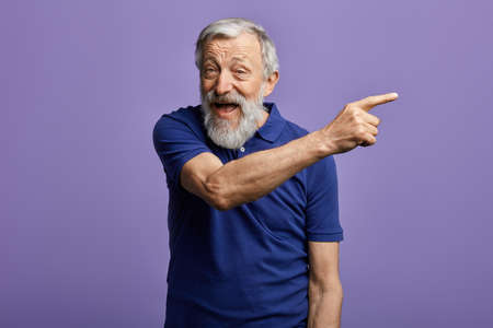 cheerful man pointing at copy space and looking at the camera. close up portrait, place for advert. happy old man indicating somewhere
