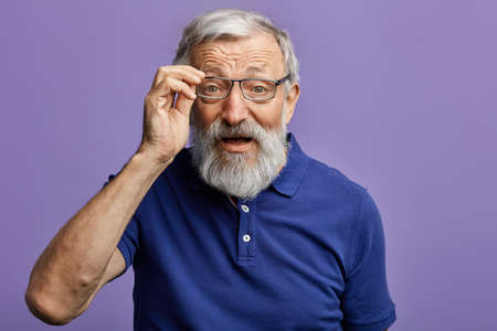 cheerful old man looking through the glasses at the camera isolated on blue background. close up portrait. studio shot.handsome man cannot recognize his grandson. man with poor eyesight.
