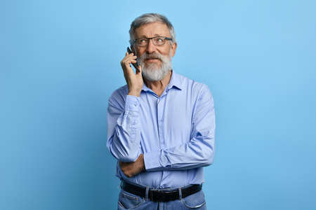 handsome senior man looking up, talking on mobile phone isolated against sky blue background. old businessman having chat, business conversation witj clients, parters. gadget concept.