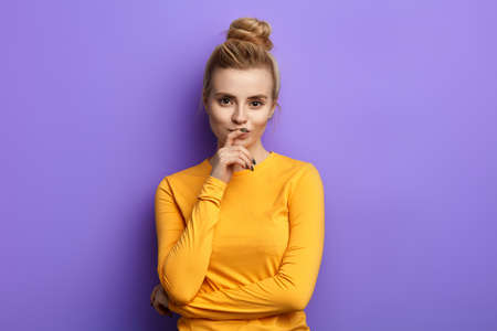 Attractive girl in casual clothes keeping hand on chin in doubt and suspicion, feeling sceptical about something, isolated blue background, studio shot Фото со стока