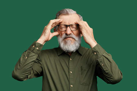unhappy man with closed eyes trying to remember some information, facts, holding his temples, man with gray beard has lost his memory. isolated green background , studio shot